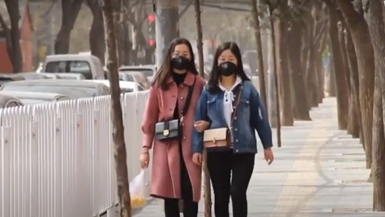 Two Chinese women in face masks walking down the street