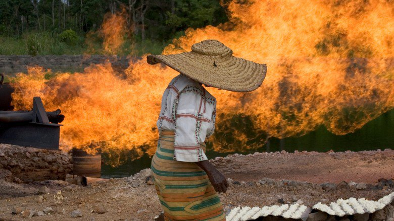 Woman stands near gas flare in Nigeria