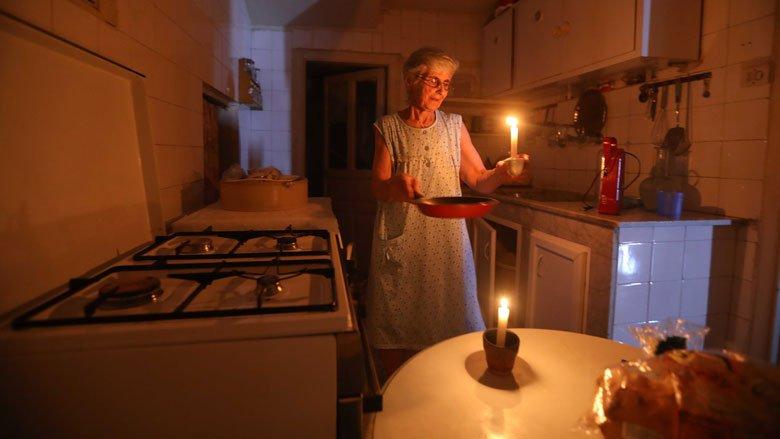 سيدة تحمل شمعة مضيئة بعد انقطاع الكهرباء عن منزلها في بيروت، لبنان.